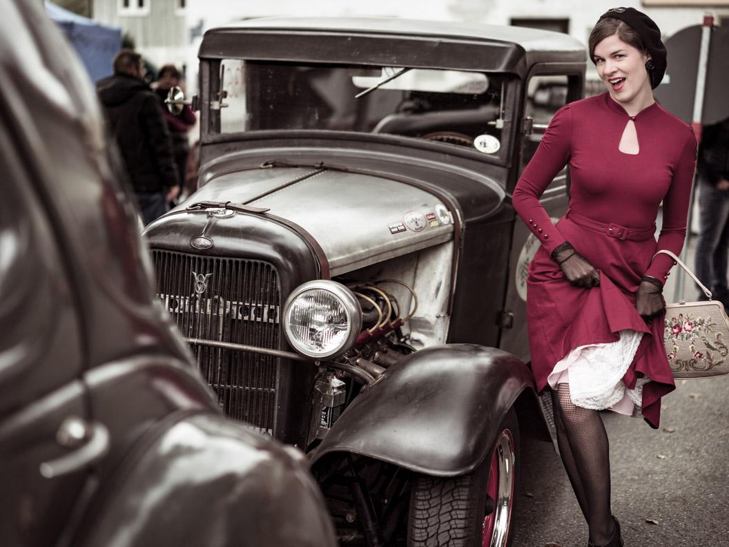 RetroCat mit Retro-Kleid und Vintage-Petticoat vor einem Oldtimer