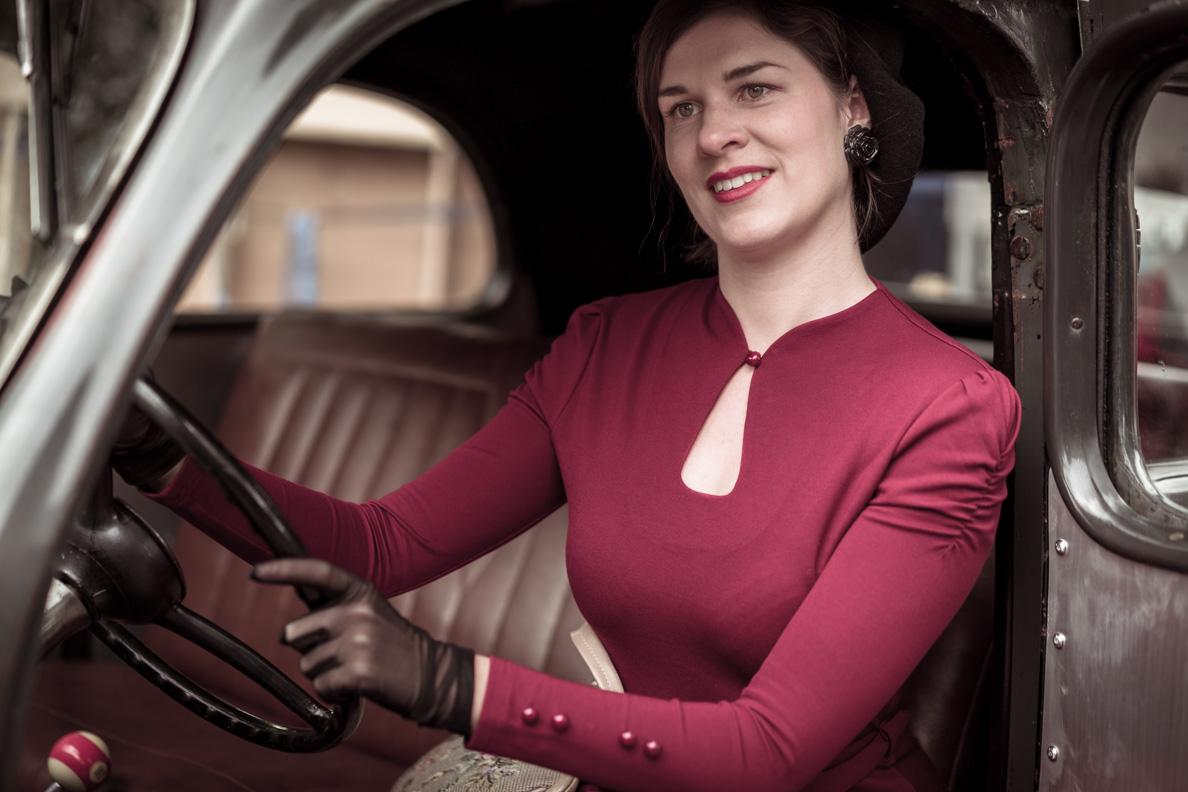 RetroCat mit einem roten 40er-Jahre-Kleid von BlackButterfly im Oldtimer