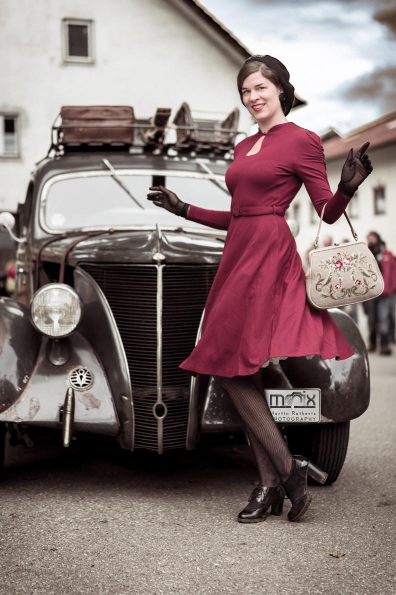 """RetroCat mit dem Swing-Kleid """"Megan"""" von BlackButterfly vor einem Oldtimer"""
