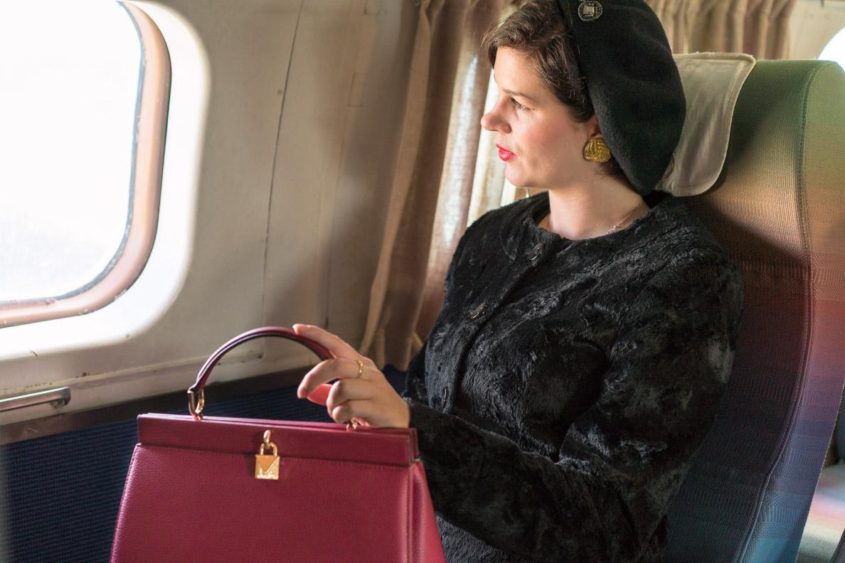 RetroCat mit einer Designertasche von Fashionette im Flugzeug
