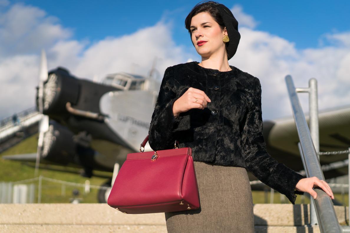 RetroCat mit einer klassischen Michael Kors Tasche von Fashionette vor einem alten Flugzeug