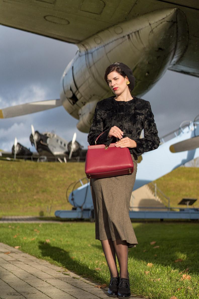 RetroCat in einem glamourösen 30er-Jahre-Outfit mit Designertasche vor einem historischen Flugzeug