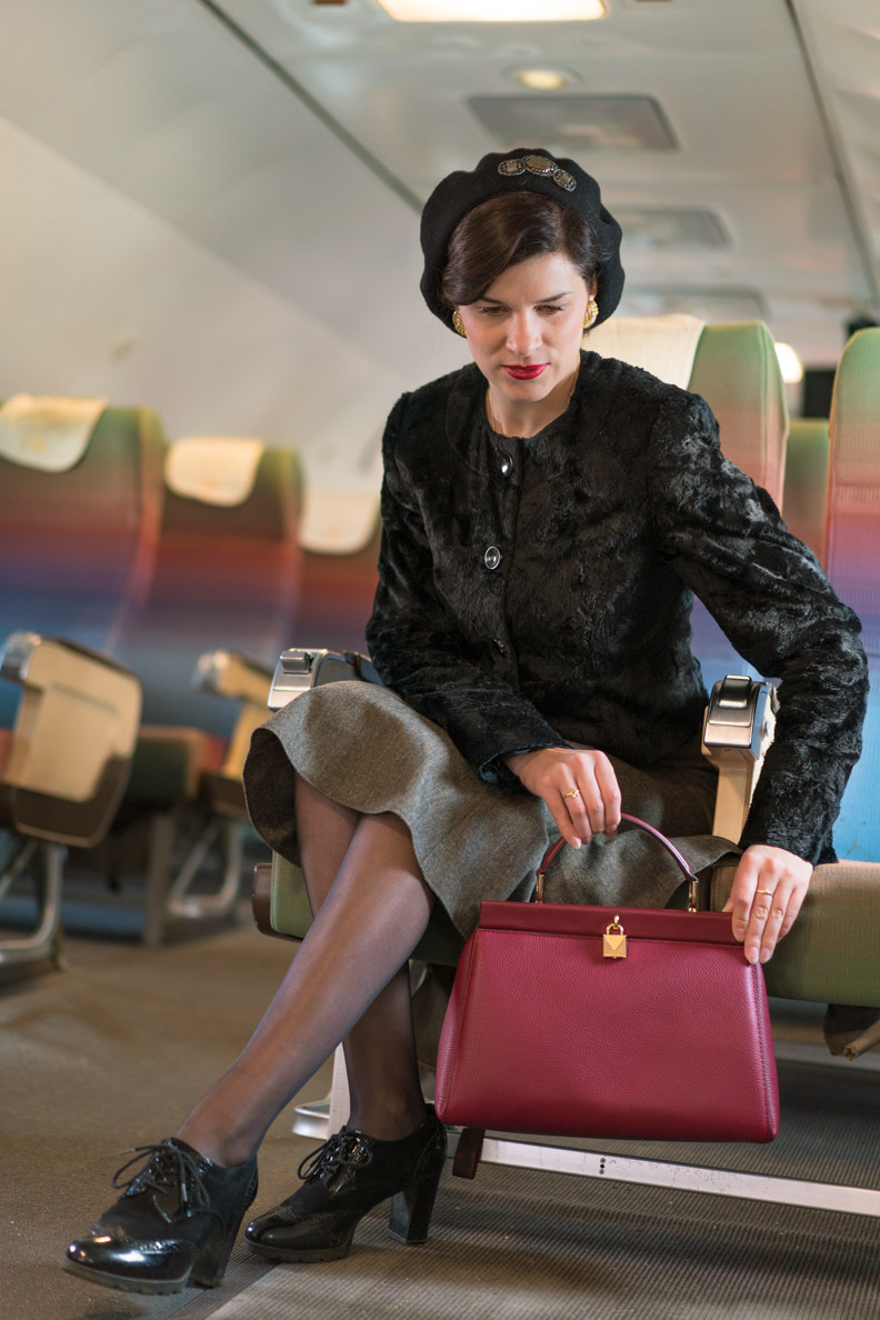 RetroCat beim Verstauen ihres eleganten Handgepäcks im Flugzeug