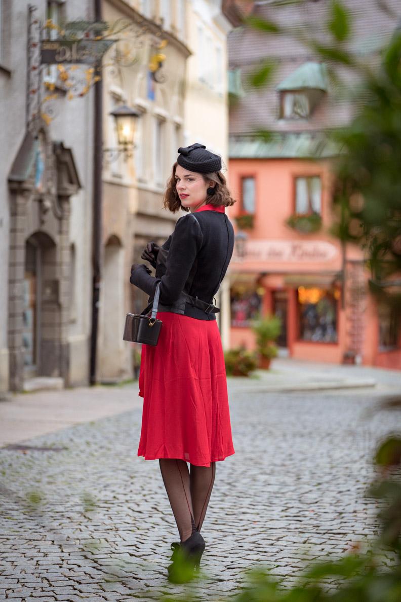 RetroCat mit rotem Kleid, Blazer und glamourösen Nahtstrümpfen in Füssen