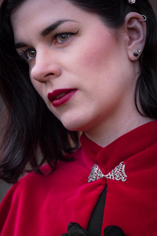 Eine Detailaufnahme von RetroCat mit dem roten Drama Cape inklusive silbernem Verschluss