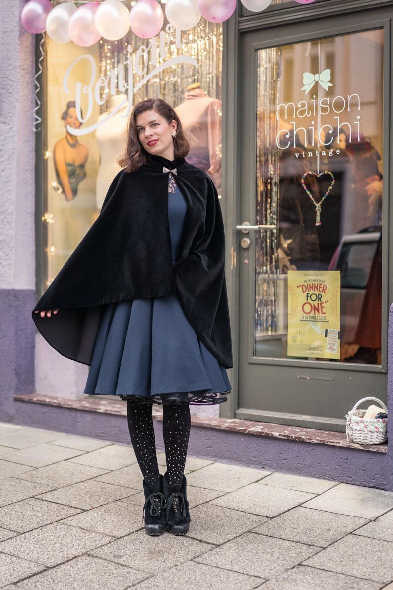 RetroCat mit Samt-Cape und Petticoatkleid vor dem Vintage-Laden Maison Chi Chi in München
