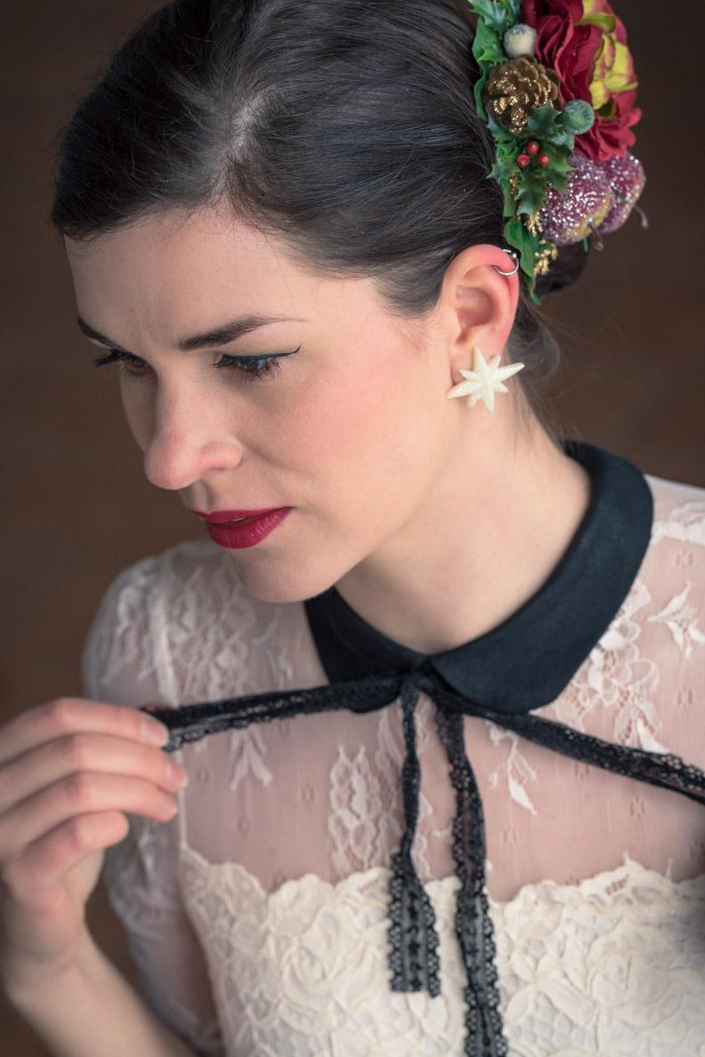 Vintage-Bloggerin RetroCat mit Sternen-Ohrringen und festlicher Haarblume
