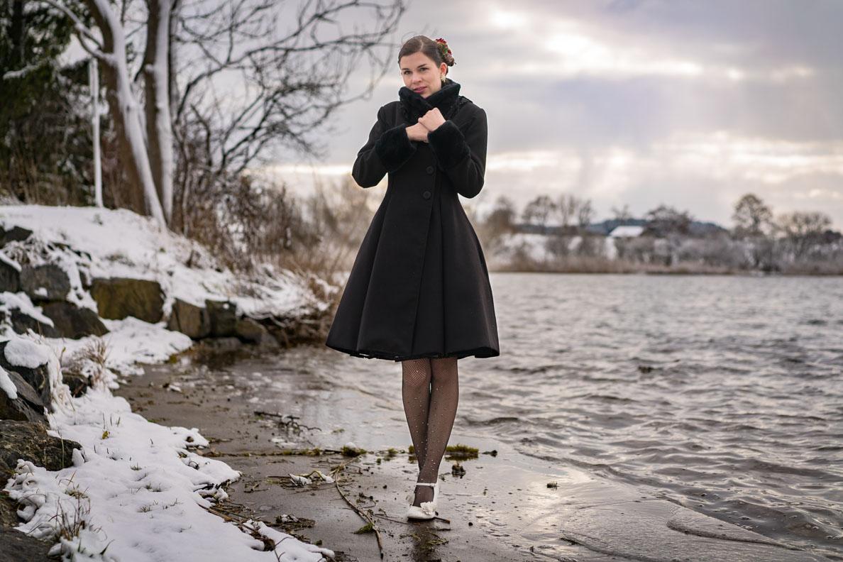 Vintage-Bloggerin RetroCat mit dem schwarzen Angeline Coat von Hell Bunny im Winter