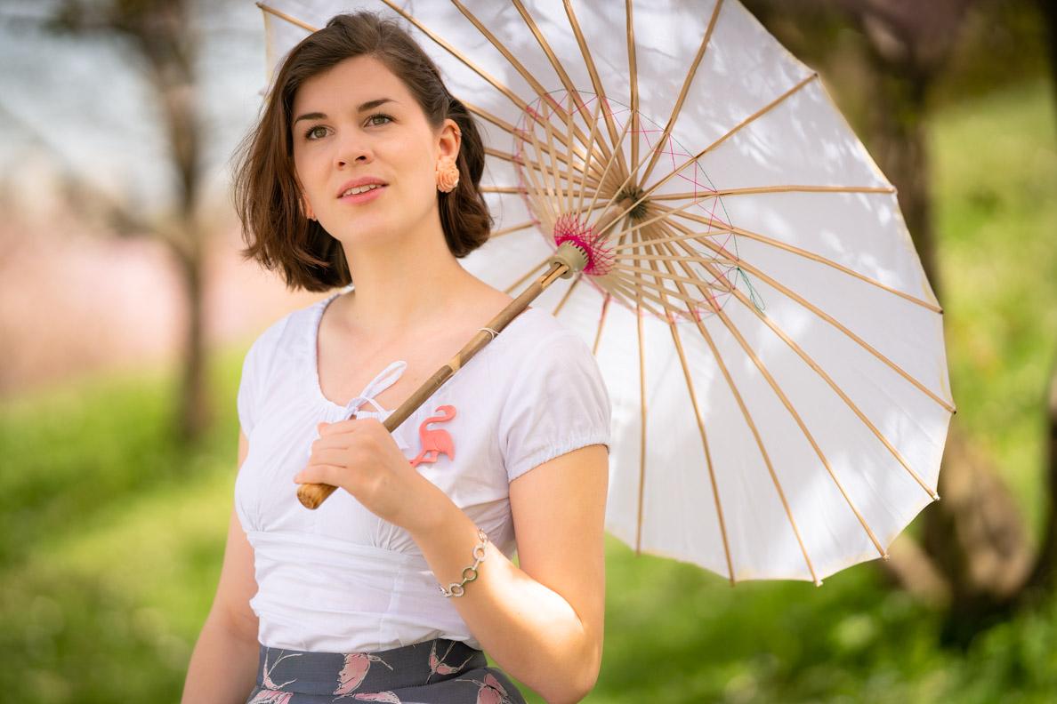 RetroCat mit Sonnenschirm, weißem Top und passenden Retro-Accessoires für den Frühling