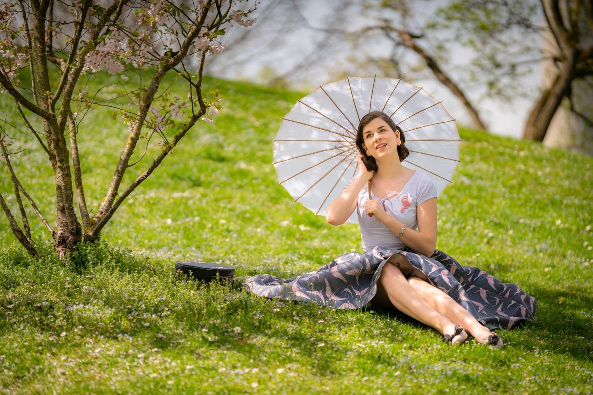 RetroCat mit Sonnenschirm im Asia-Stil und einem frühlingshaften Retro-Outfit im Park