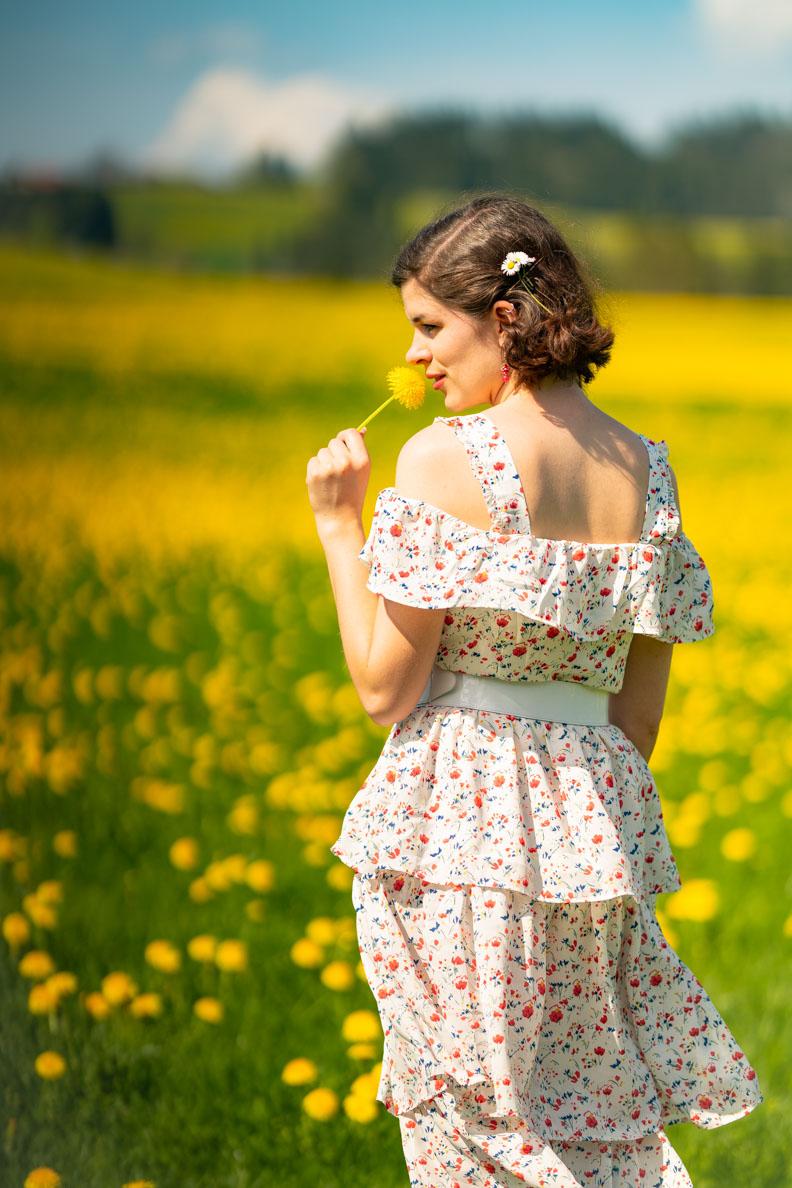 Sandra vom Vintage-Blog RetroCat in einem Boho-Kleid auf einem Feld mit blühendem Löwenzahn