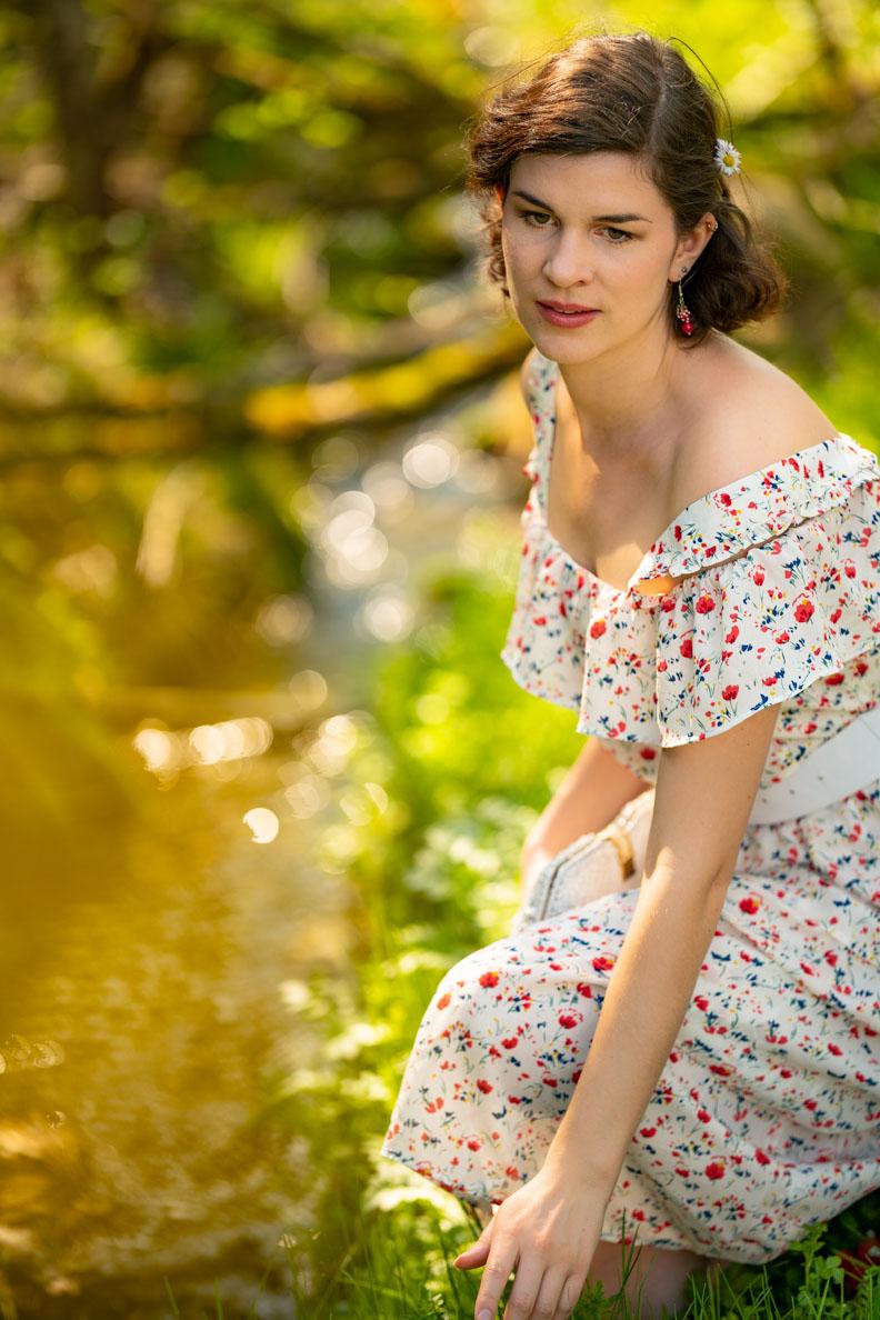 Vintage-Mode- und Beauty-Bloggerin RetroCat mit einem romantischen Outfit und Make-up in der Natur