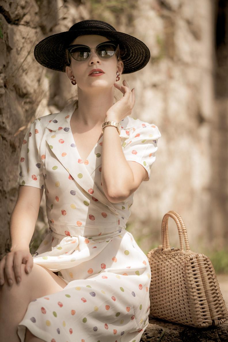 Vintage-Mode-Bloggerin RetroCat mit Wickelkleid, großem Hut und Cateye-Sonnenbrille im Retro-Stil