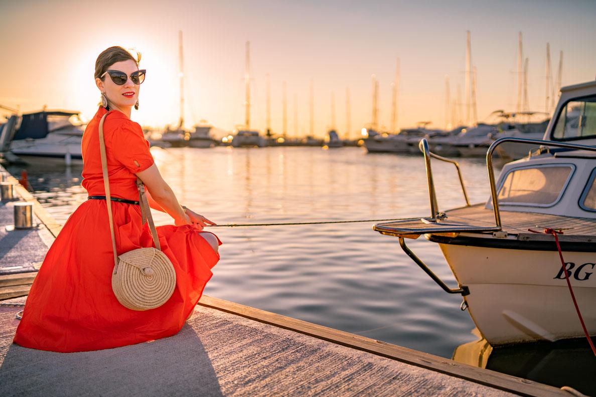 Vintage-Bloggerin RetroCat mit einem orange-roten Kleid von Joanie Clothing am Hafen von Biograd