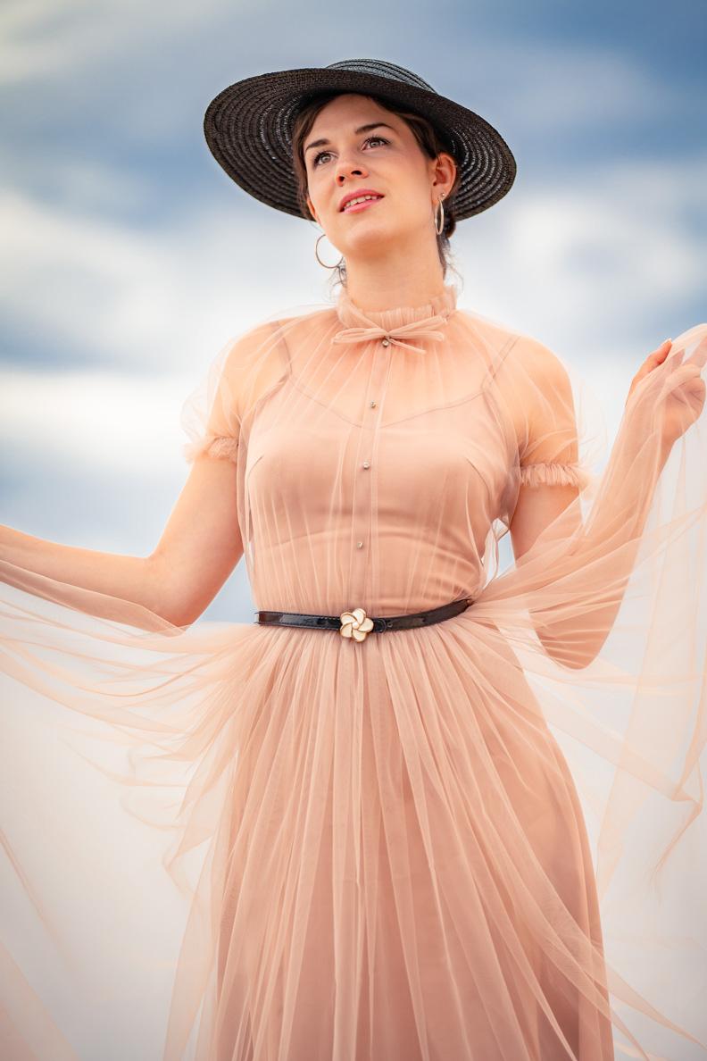 Vintage- und Beauty-Bloggerin RetroCat mit einem rosa Tüllkleid, einem zarten Gürtel und einem Vintage-Strohhut aus den 50er-Jahren
