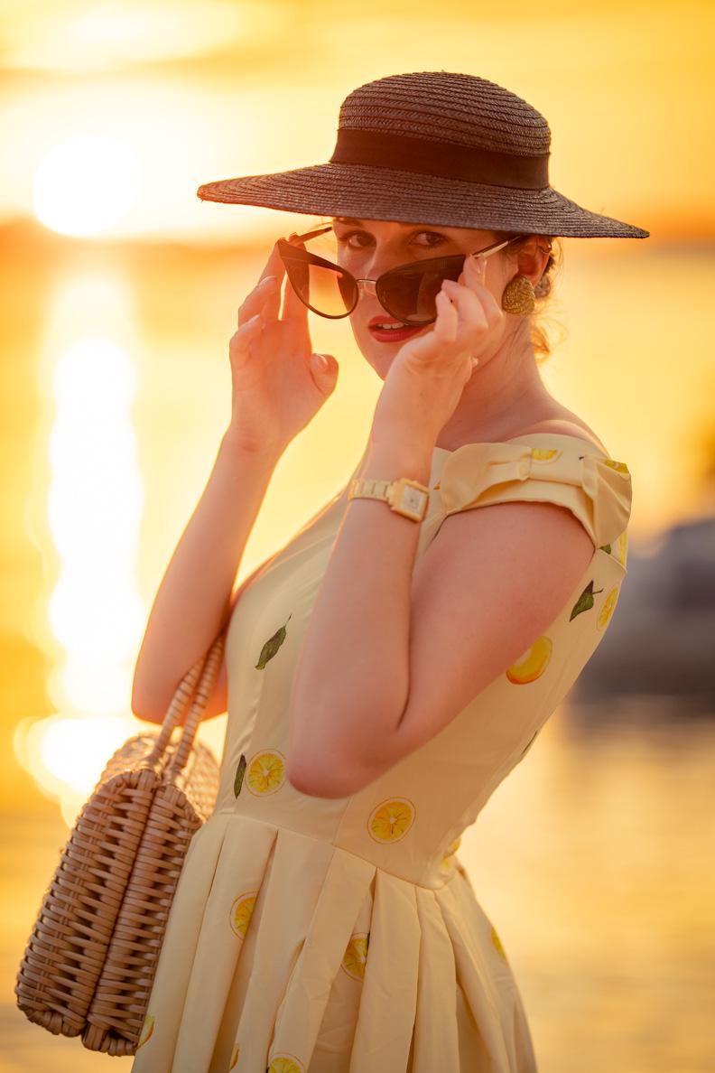 Vintage-Bloggerin RetroCat mit Zitronen-Kleid, Cateye-Sonnenbrille von Dolce & Gabbana und einem Vintage-Strohhut aus den 50ern