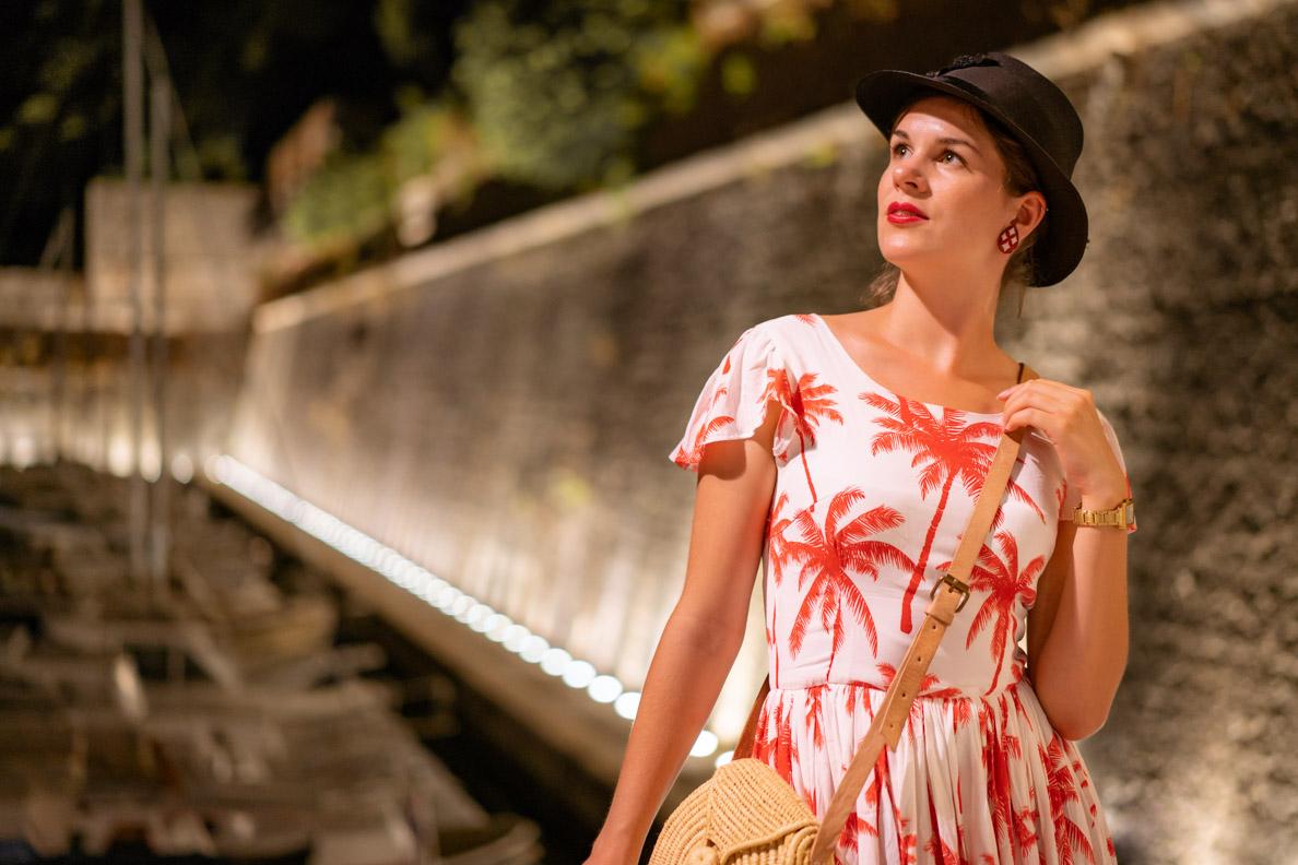 Vintage-Bloggerin RetroCat mit Strohtasche, Vintage-Hut und Palmen-Kleid