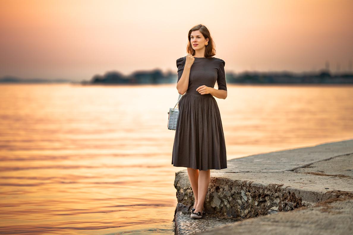 Vintage-Mode-Bloggerin RetroCat mit einem grauen Retro-Kleid vor dem Sonnenuntergang in Kroatien