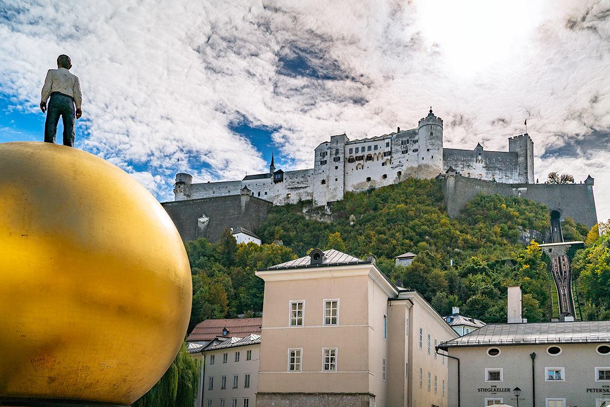 Die Festung Hohensalzburg mit einer goldenen Kugel mit männlicher Figur im Vordergrund