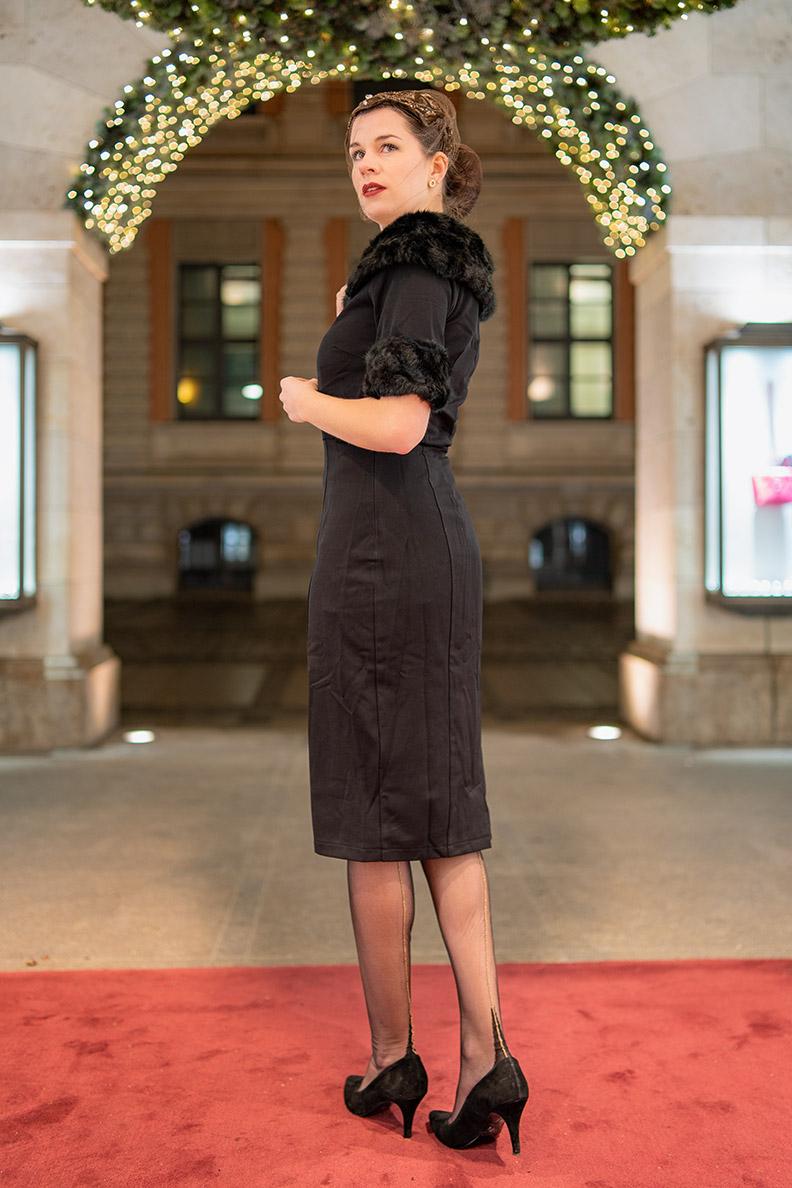Vintage-Fashion-Bloggerin RetroCat in einem Weihnachts-Outfit mit Retro-Kleid und Nahtstrümpfen
