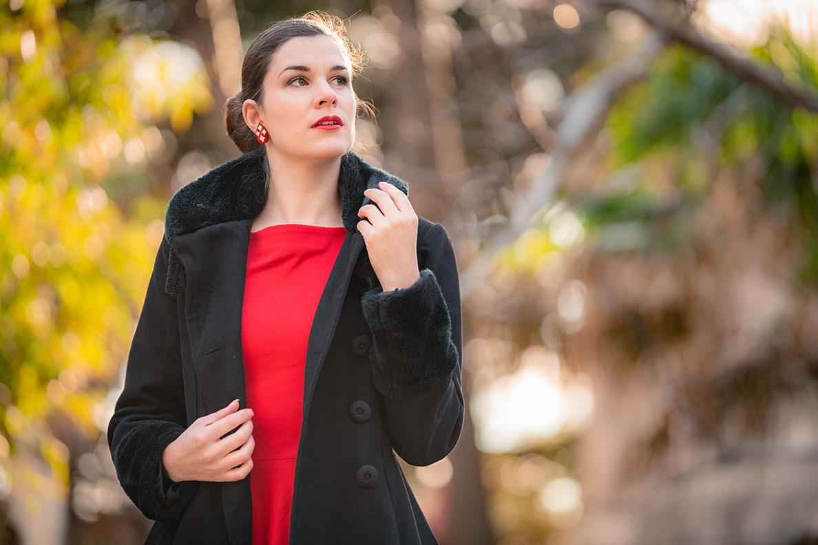 Fashion-Bloggerin RetroCat mit rotem Kleid und schwarzem Retro-Mantel