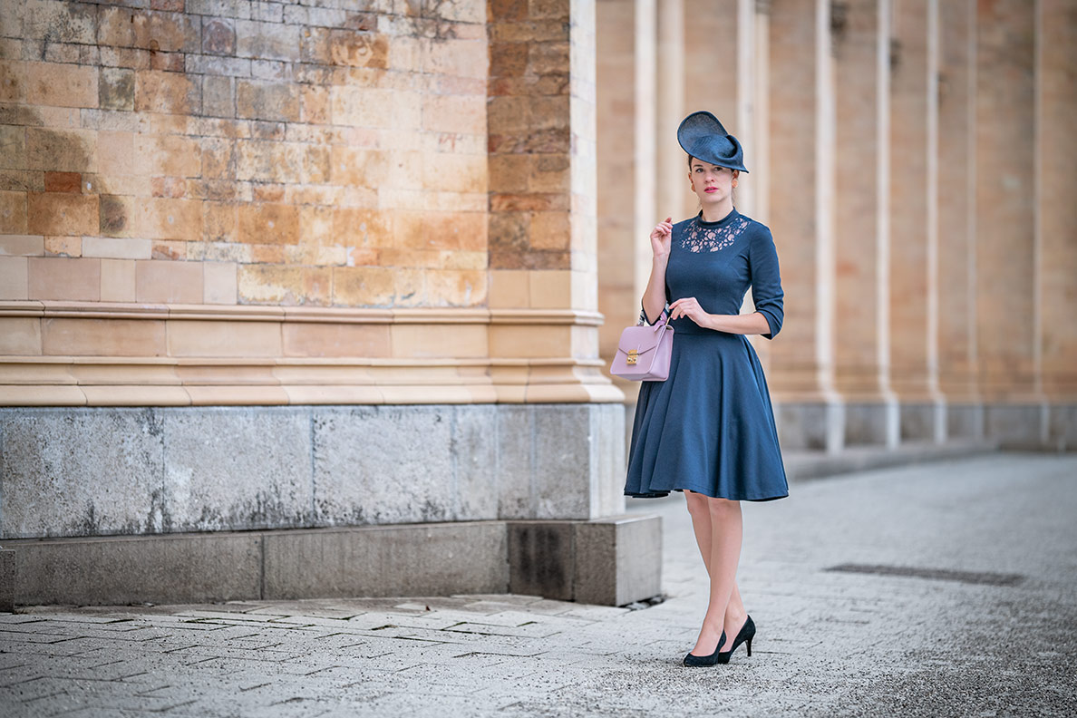 Fashion-Bloggerin RetroCat in einem stilvollen Retro-Outfit mit Fascinator