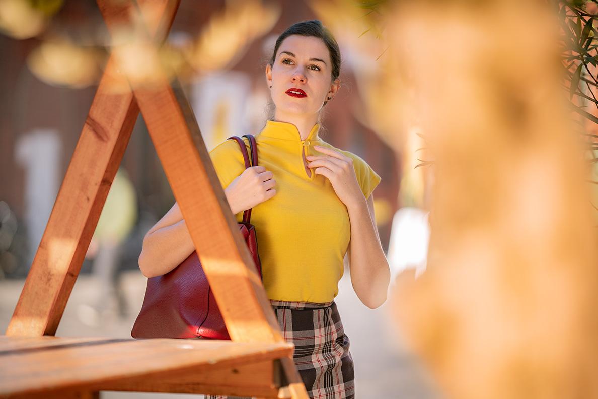 Sandra vom Mode-Blog RetroCat mit gelbem Top und roter Tasche