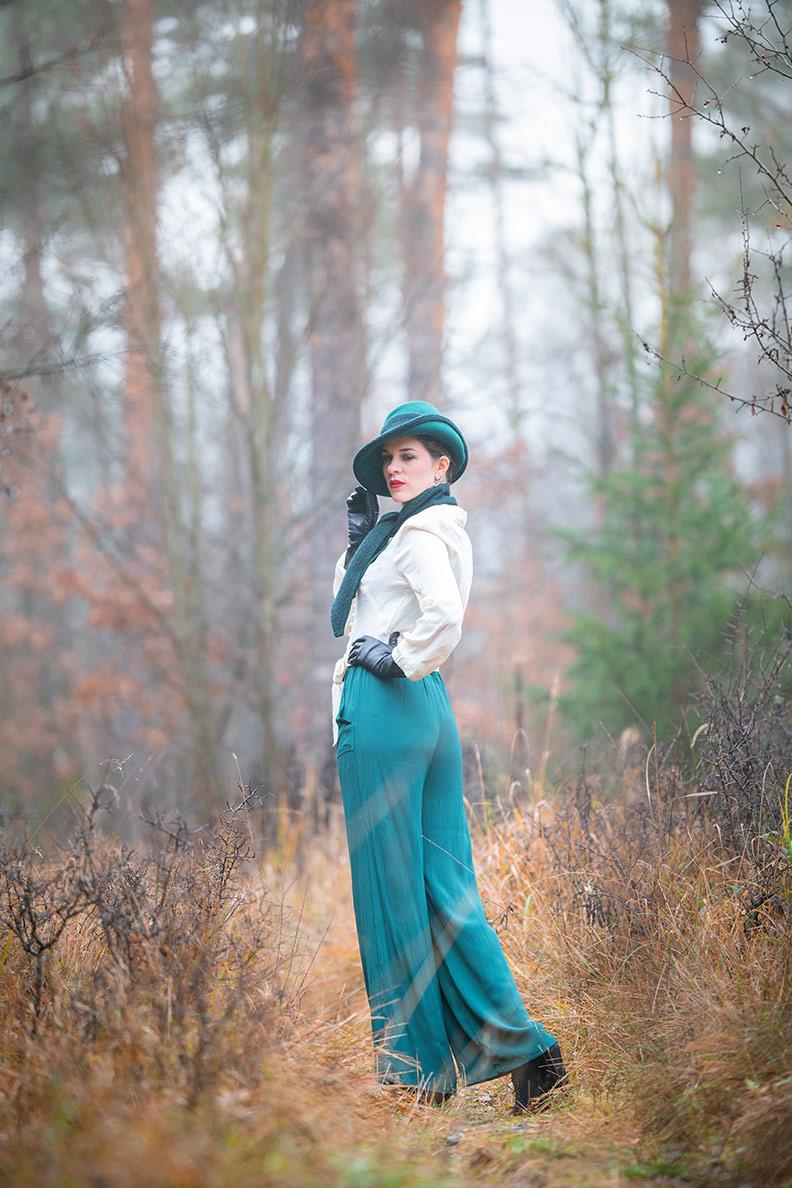 RetroCat in einem 30er-Jahre-Outfit mit Hose, Bluse und Hut