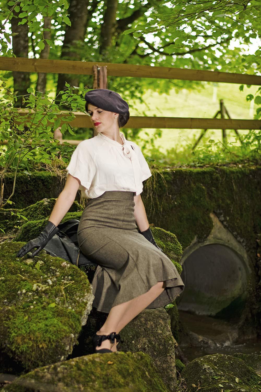 RetroCat in einem 30er-Jahre-Outfit bestehend aus Rock und Bluse mit Volant-Ärmeln