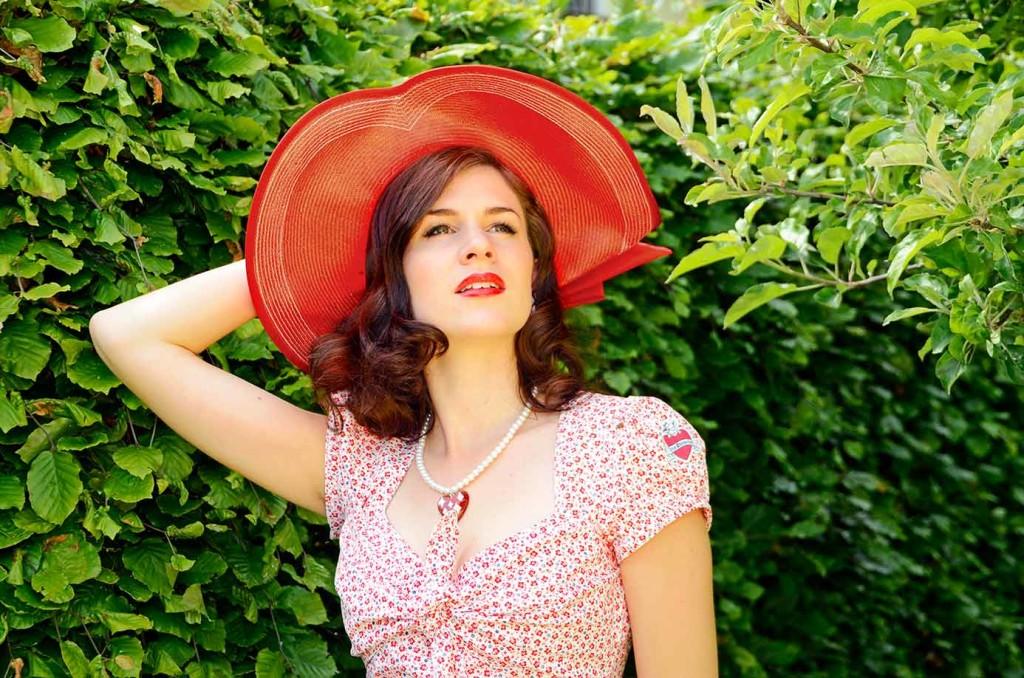 Mode-Bloggerin RetroCat mit einem roten Strohhut aus den 1950ern