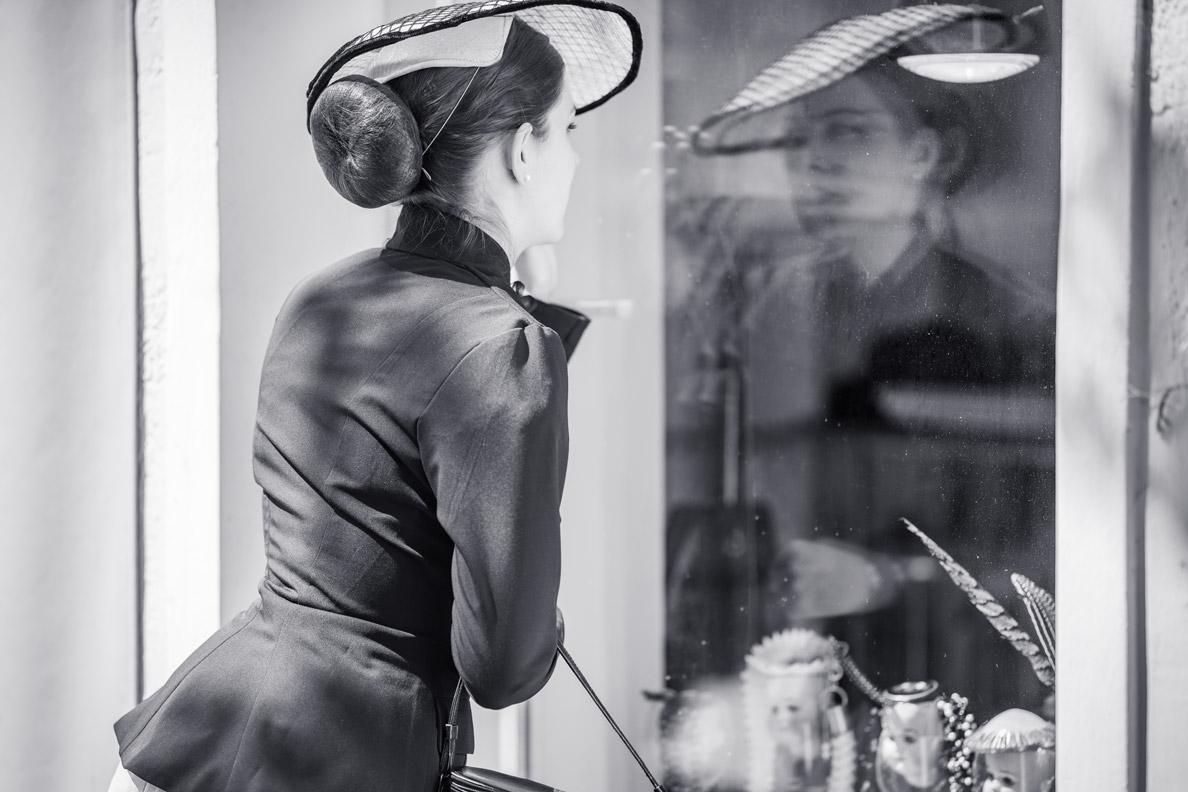 RetroCat blickt mit schwarzem Blazer und New-Look-Hut in ein Münchner Schaufenster