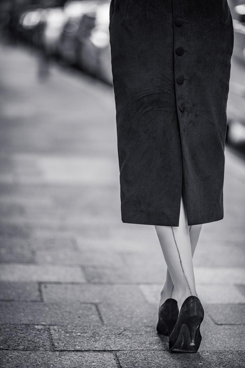 RetroCat mit Nahtstrümpfen und einem Kleid mit Knöpfen an der Rückseite