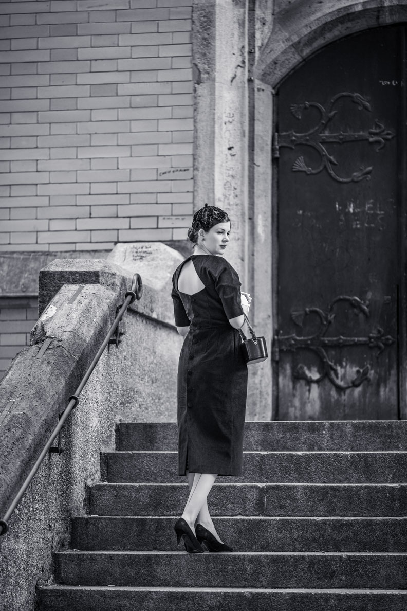 RetroCat in einem schmal geschnittenen Kleid von Ginger Jackie auf einer Treppe