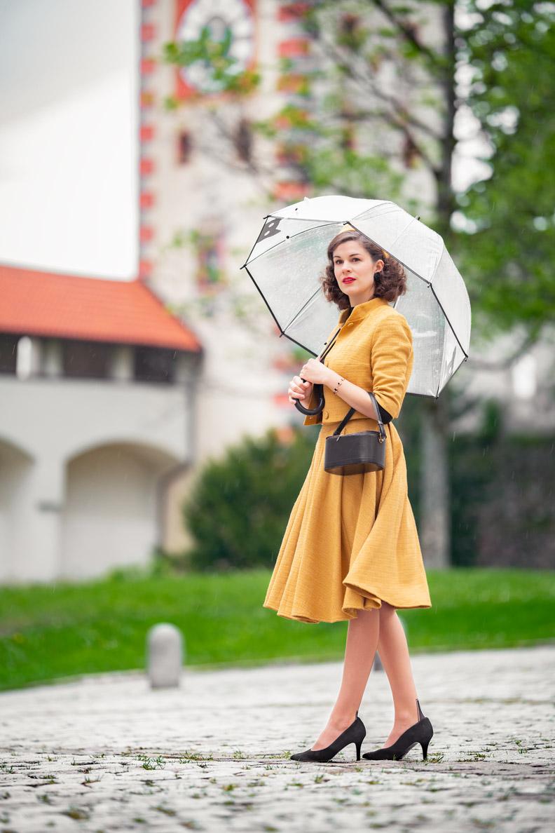Vintage-Model RetroCat mit Rock und passender Jacke, einer Vintage-Tasche und einem transparenten Regenschirm