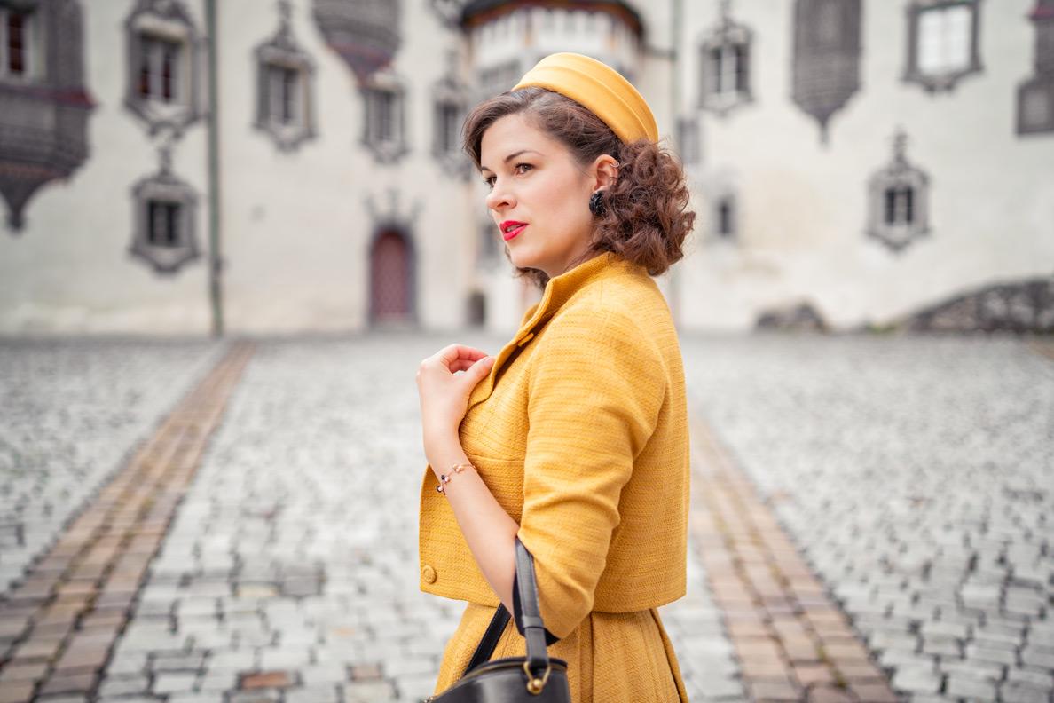 RetroCat mit einer Jacke, Locken im Vintage-Stil und einem passenden Pillbox-Hut von Miranda's Choice