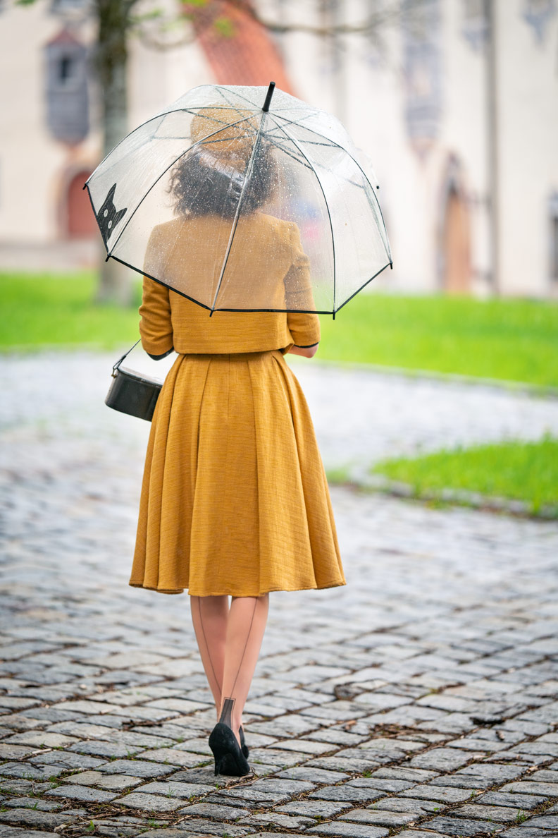 Vintage-Mode-Bloggerin RetroCat mit einem senfgelben Kostüm von Gracy Q, einem transparenten Regenschirm und Nahtstrümpfen in Füssen