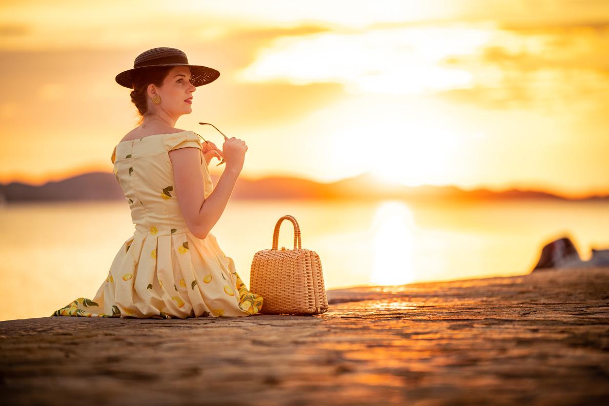 RetroCat bewundert mit Sommerkleid, hochgesteckten Haaren und einem Hut den Sonnenuntergang