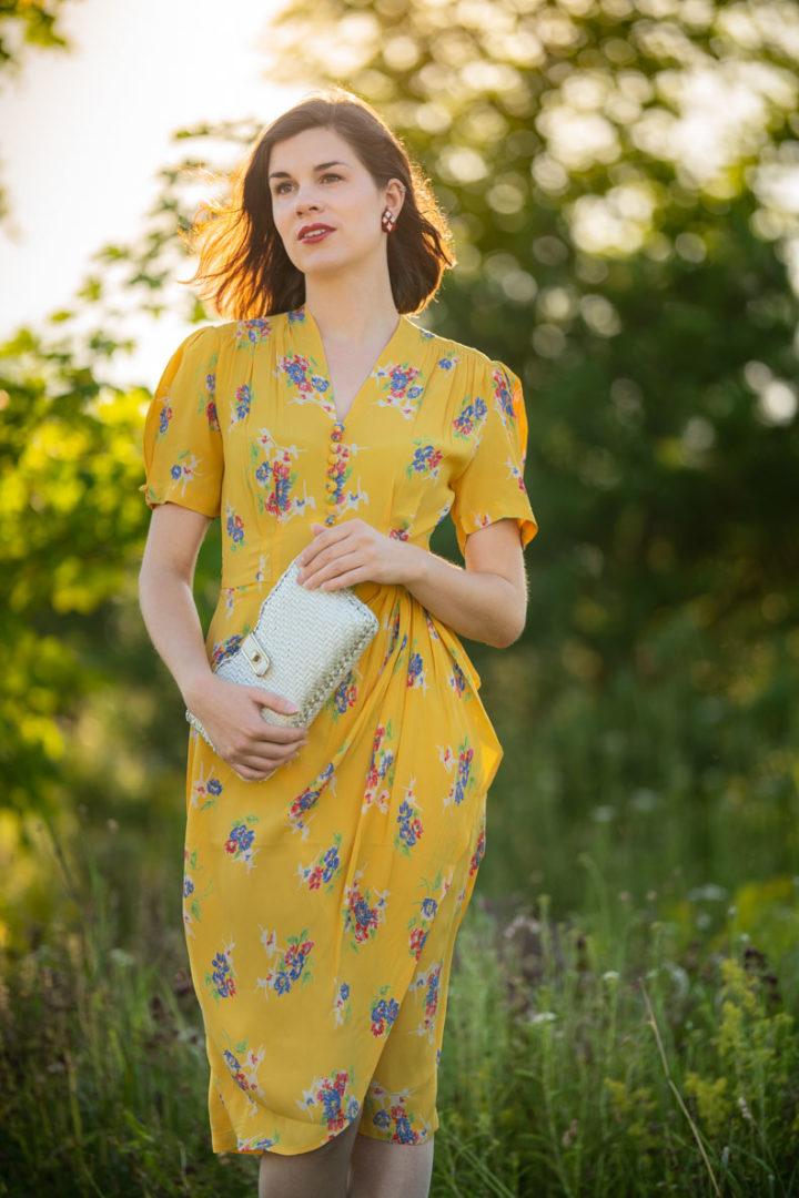 Vintage-Bloggerin RetroCat mit Sommerkleid und kleiner Korbtasche in Form einer Clutch