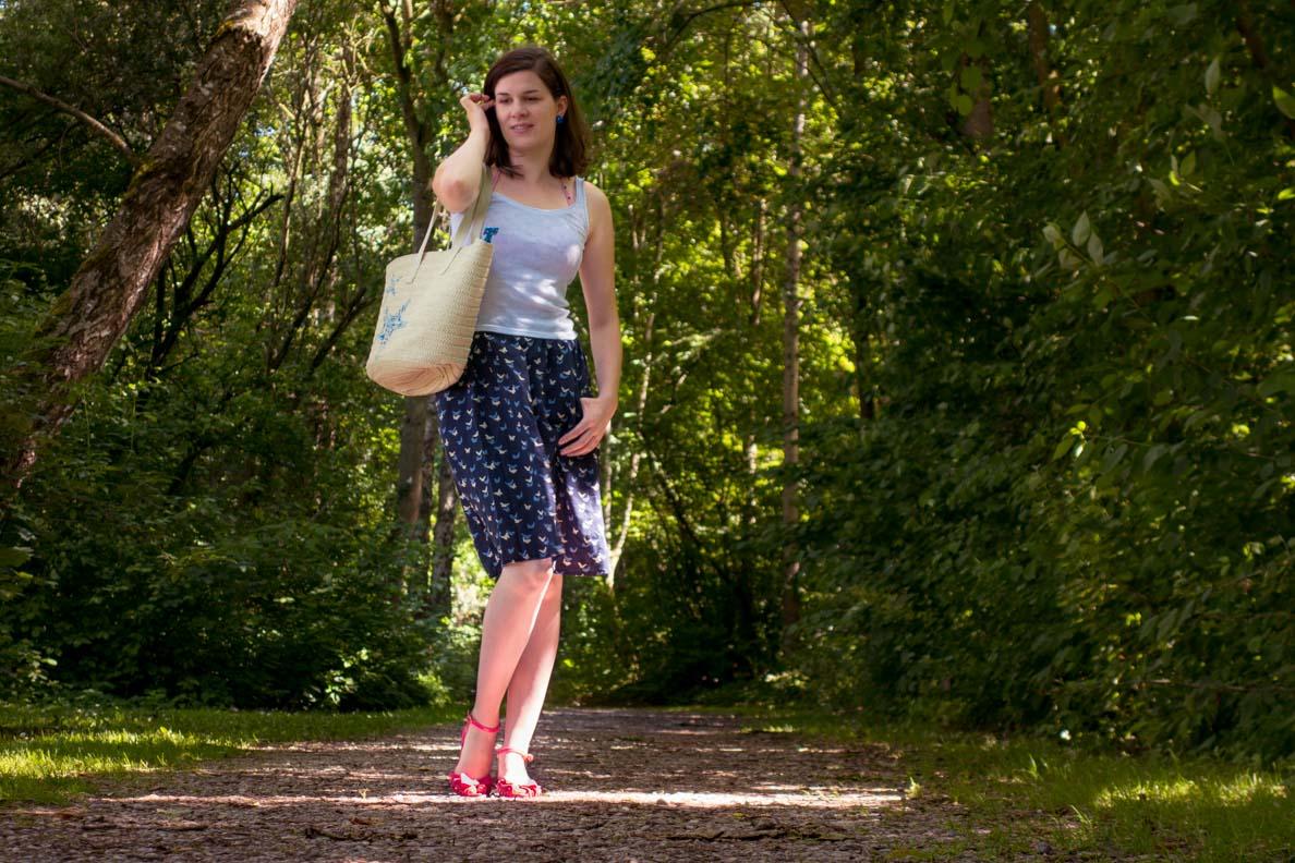 RetroCat mit einer Strandtasche aus Stroh und einem schlichten Tages-Outfit