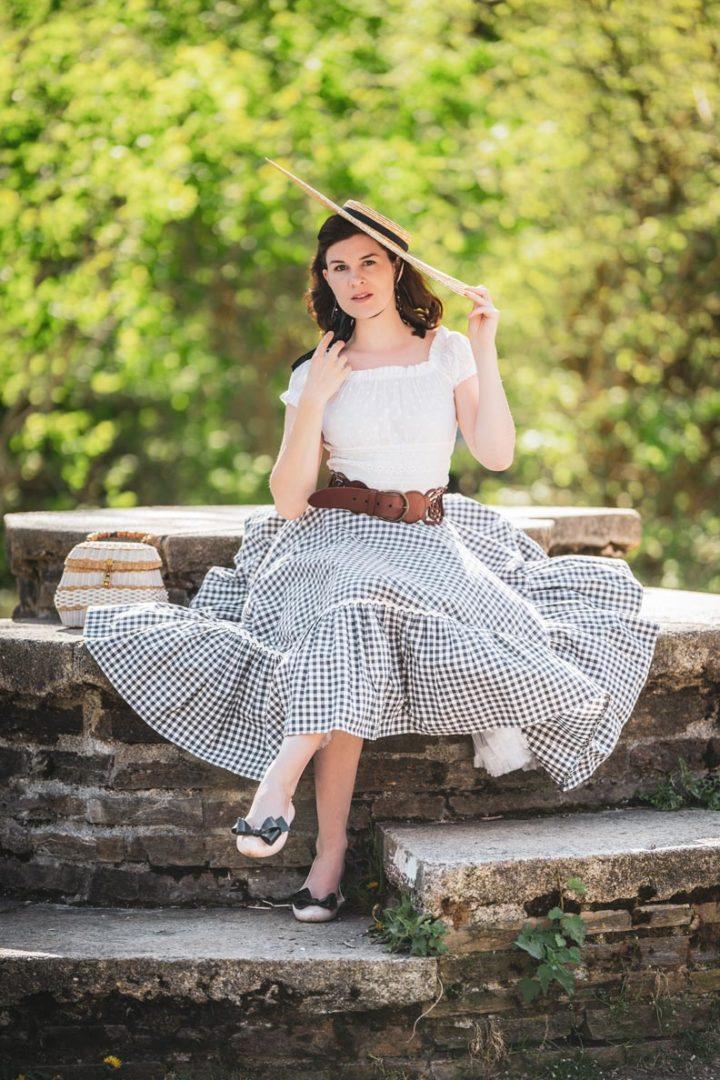 Vintage-Mode-Bloggerin RetroCat in einem eleganten Sommer-Outfit mit Korbtasche und Strohhut