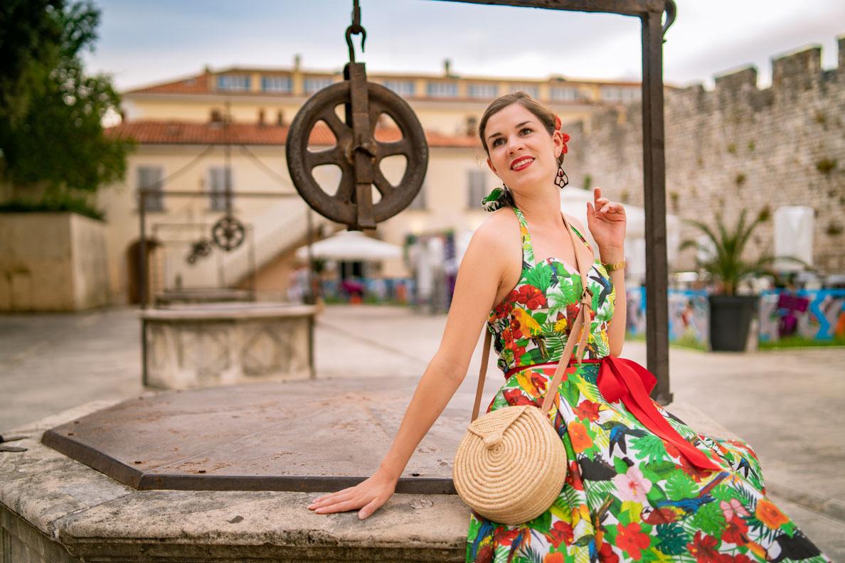 RetroCat mit einer runden Strohtasche und einem bunten Sommerkleid in Zadar
