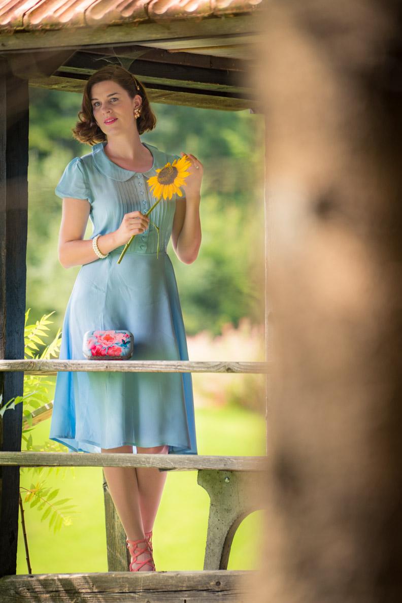 Tipps für coole Sommer-Outfits: RetroCat mit einem blauen Kleid aus Crêpe de Chine und einer Sonnenblume