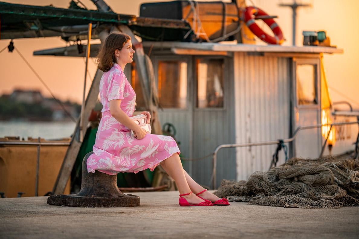 Fashion-Bloggerin RetroCat mit flachen Sandalen und einem rosa Kleid vor einem Fischkutter
