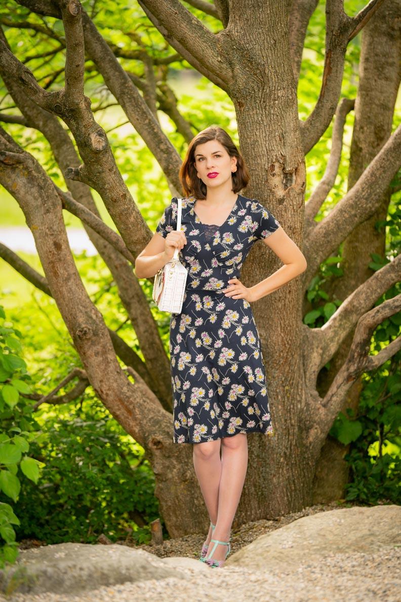 RetroCat in einem Jerseykleid mit Blumenprint von Vive Maria vor einem Baum