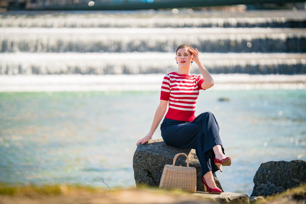 RetroCat mit einer sommerlichen Marlene-Hose, einem roten Streifenshirt und passenden Accessoires vor einem Wasserfall