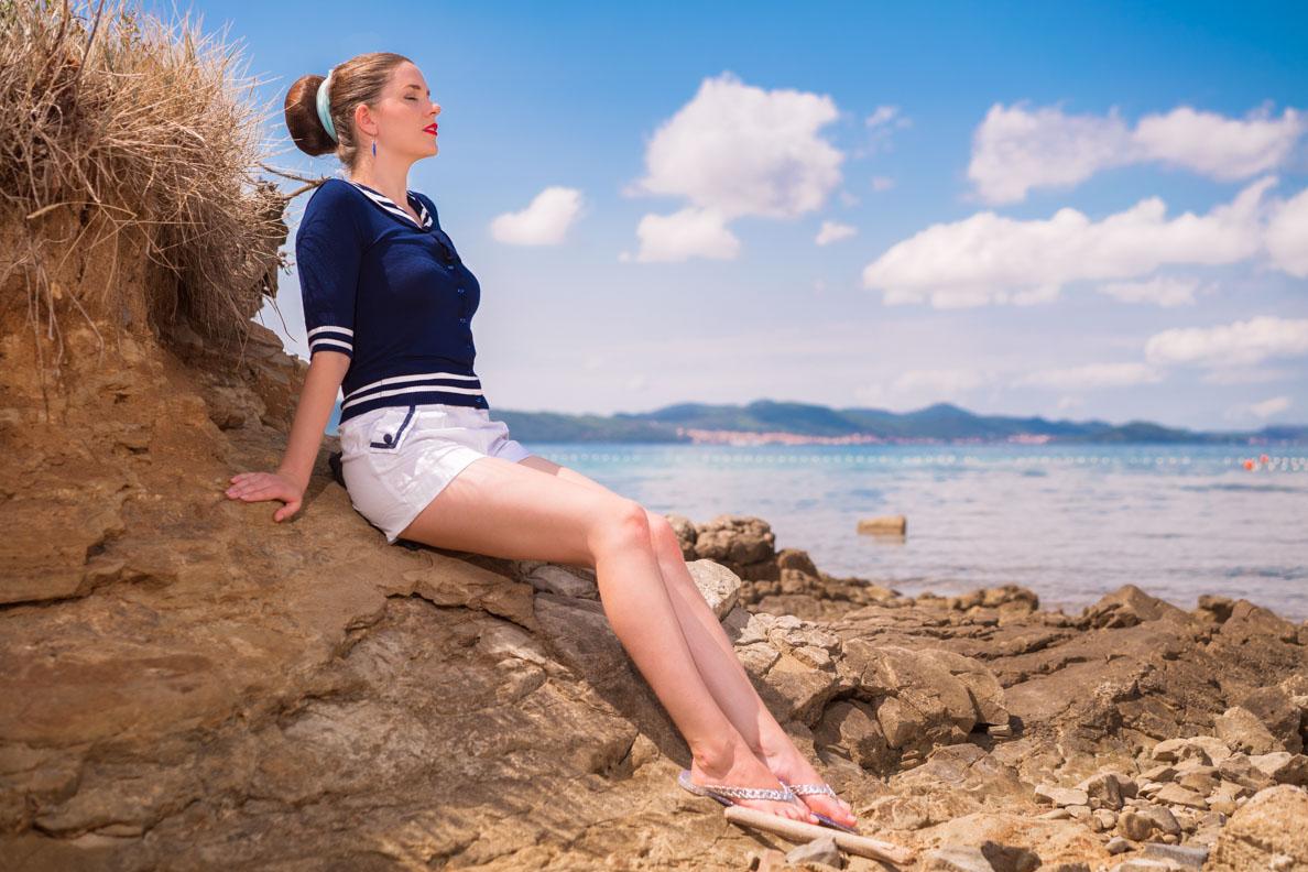 RetroCat mit Shorts und einem Segler-Top beim Sonnen am Strand in Kroatien
