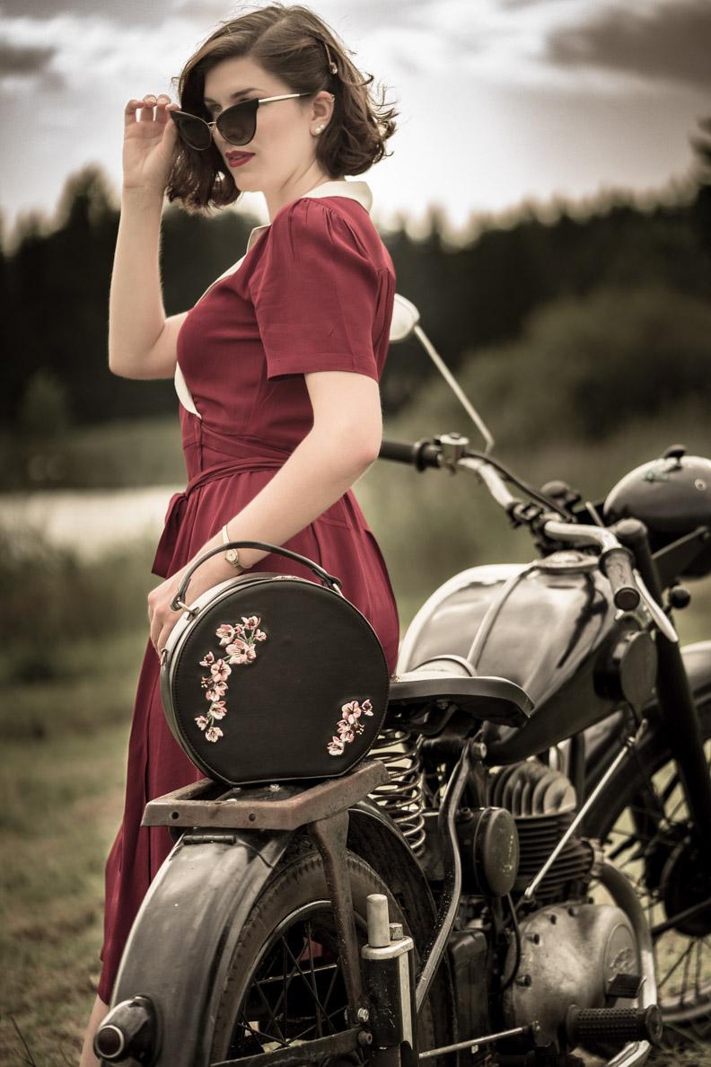 RetroCat mit dem dunkelroten Peggy Wrap Dress, einer runden Tasche und Cat-Eye-Sonnenbrille vor einem Motorrad