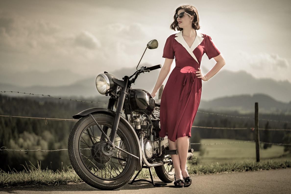 RetroCat mit einem perfekt sitzenden Wickelkleid von The Seamstress of Bloomsbury mit einem Oldtimer-Motorrad