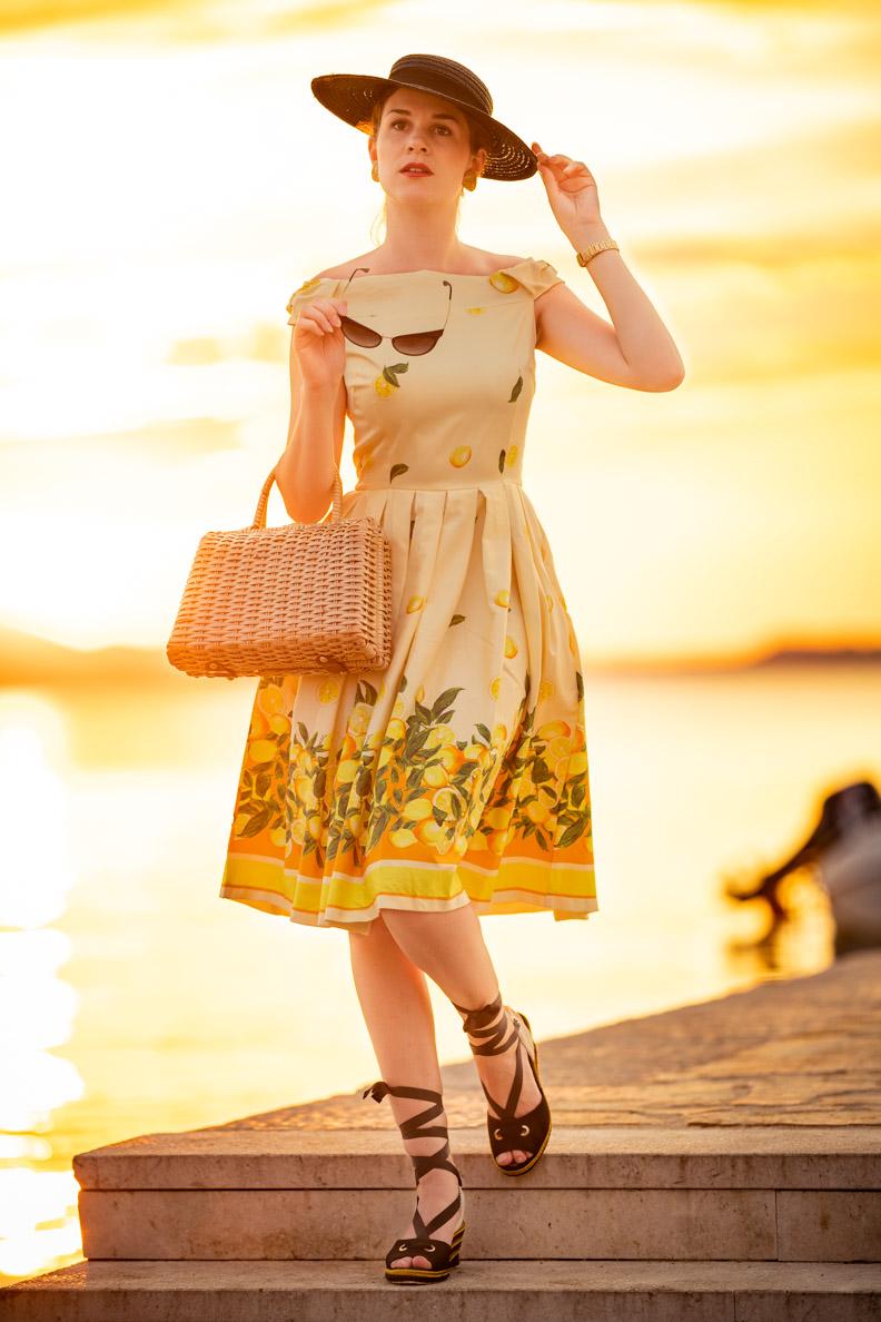 RetroCat in einem gelben Zitronen-Kleid in Kroatien, dazu trägt sie Korbtasche und Hut