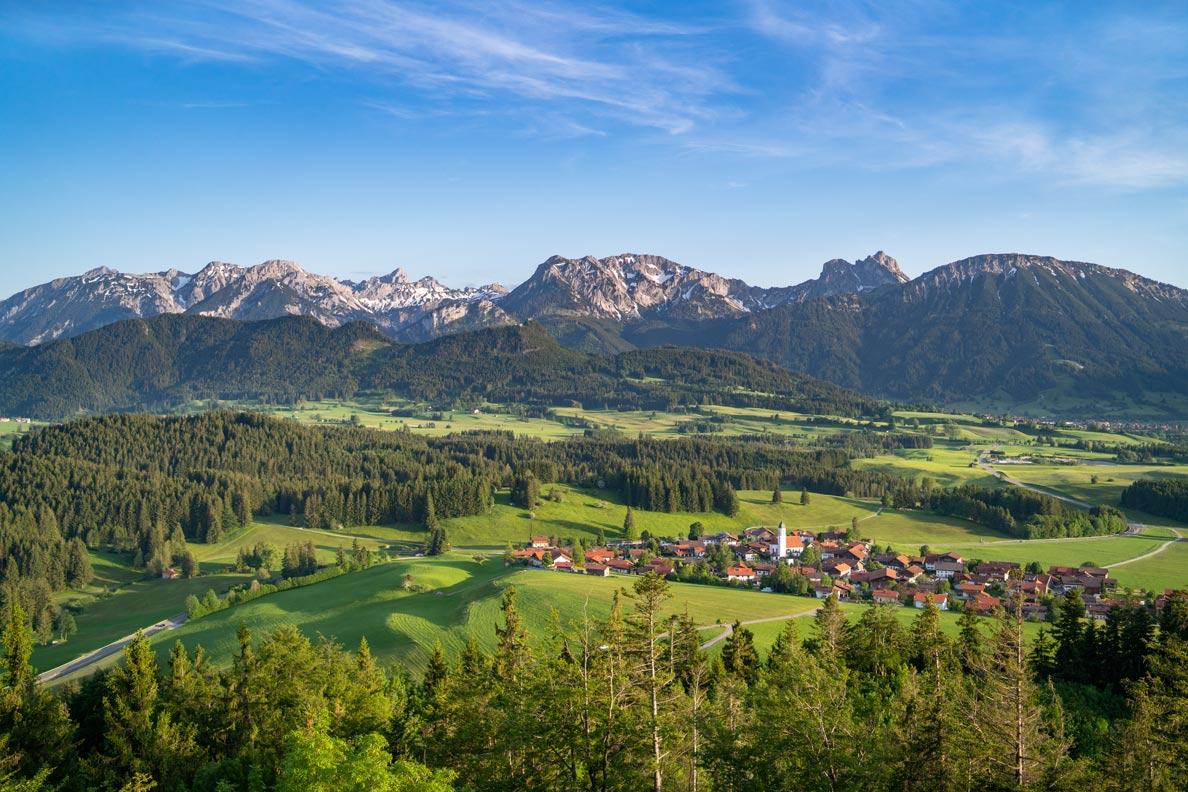 Sommerfrische in Bayern: Blick auf die Berge und ein kleines Dorf im Voralpenland
